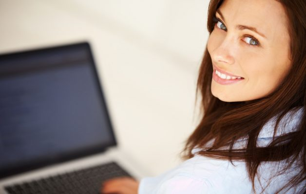 Closeup of beautiful business woman using laptop while looking at you